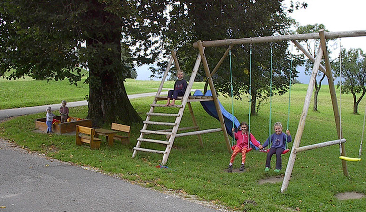 Playground in the lawn, under the tree is a sand box and a benches with a table. Next to it is a swingset with a slide