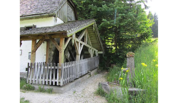 Blick auf die Mühle, seitlich ein alter Holzbrunnen, Wiese