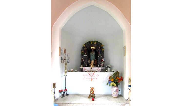 Blick auf den Altar mit Kerzen, Blumen, im Hintergrund eine Heiligenfigur