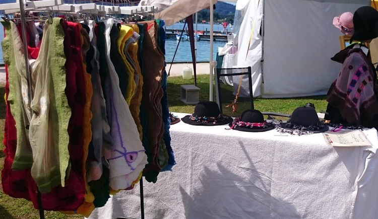 Clothes on a stand, sale table with felted hats