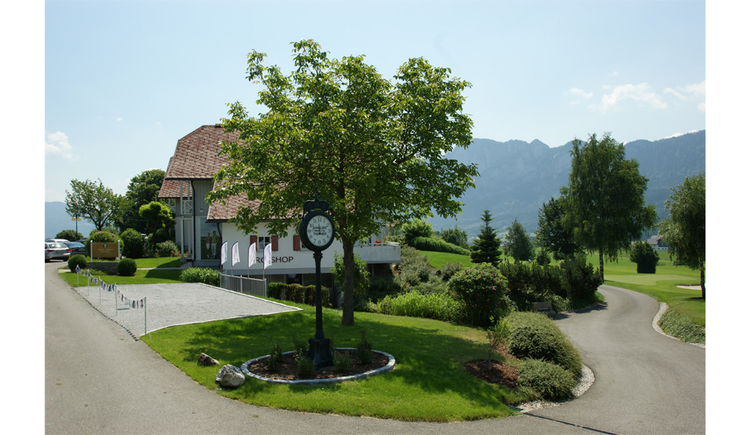 View of the house, in the foreground a large grandfather clock, trees, meadows, in the background mountains