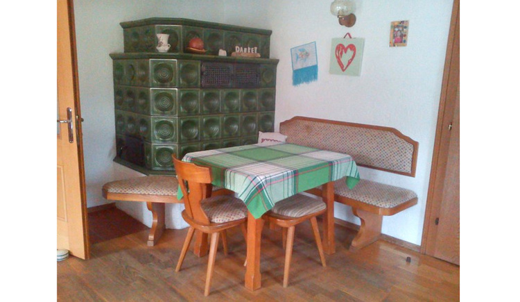Table with bench and chair, in the background a tiled stove