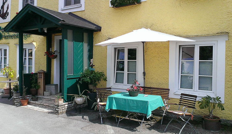 Covered entrance to the Seepension, in front of the house is a table and chairs and parasol, plants