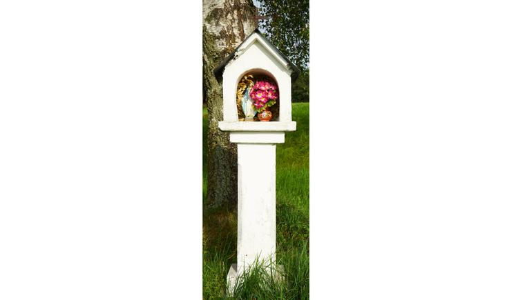 Blick auf das gemauerte Marterl, darinnen befinden sich Blumen, im Hintergrund eine Wiese