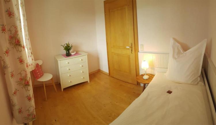 Einzelbett, seitlich eine Kommode, im Hintergrund eine Tür