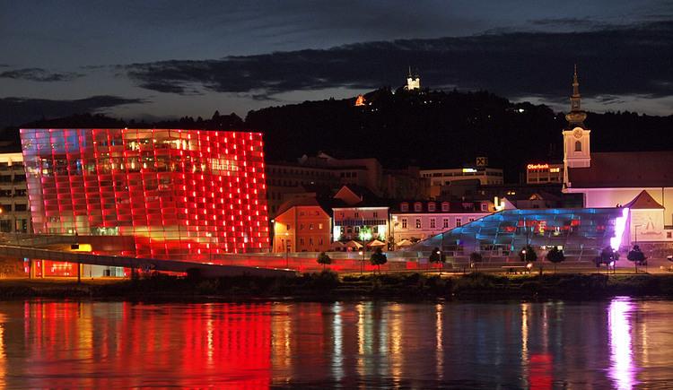 Rot beleuchtetes Ars Electronica Center von außen in der Nacht. (© Ars Electronica Center)