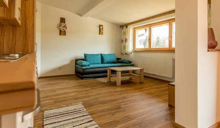 Wohnbereich mit Couch und Tisch, seitlich ein großes Fenster