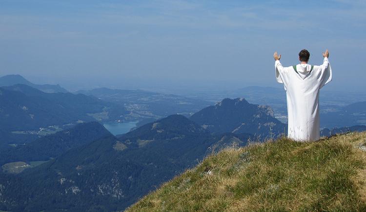 Links im Bild steht mit dem Rücken zum Betrachter ein Priester im Messgewand. Dahinter ein traumhaftes Panorama der Salzkammergut Berge. Zu erkennen ist auch der Fuschlsee.