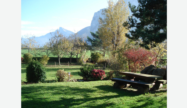 Garden, on the side benches and a table, flowers, bushes and in the background mountains.