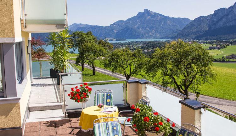 Terrasse mit Tisch und Stühle, Blumen, herrlicher Blick auf die Landschaft mit Bäumen, im Hintergrund der See und die Berge