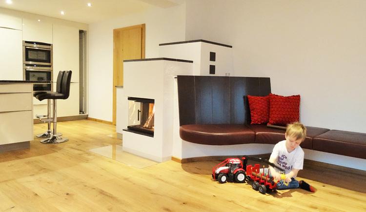 Blick in den Wohnbereich mit Kachelofen mit Ofenbank, spielendem Kind im Vordergrund, im Hintergrund die Küche