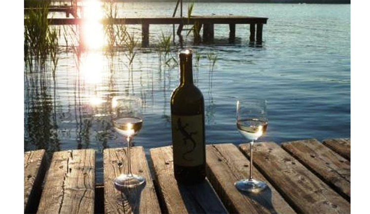 glasses and a bottle of wine on the footbridge, sunset and the lake in the background