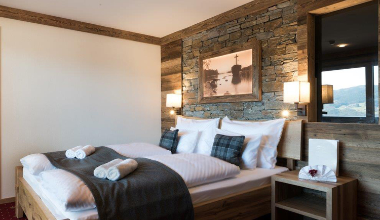 Hotelzimmer im urig-modernen Stil, mit Doppelbett und Nachtkästchen