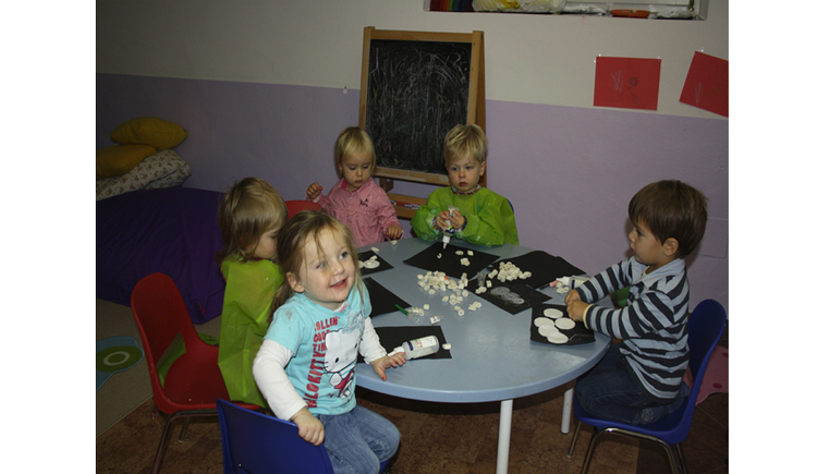 children sit on a table and do handicrafts