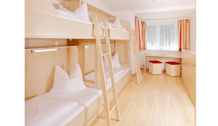 Schlafzimmer mit einzelnen Stockbetten, Leiter, im Hintergrund ein länglicher Tisch mit Hocker, Fenster, seitlich ein Schrank\n