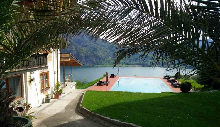 view on the pool, side a small part of the house, in the background lake and mountains \n
