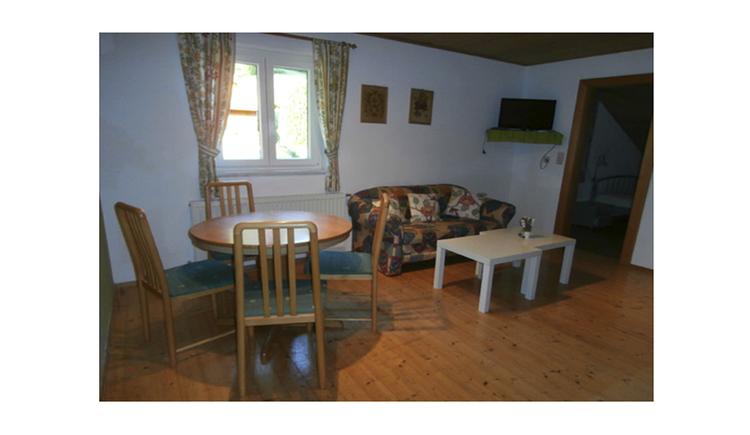 im Hintergrund kleine Couch mit Tisch, Fenster, davor ein Esstisch mit Stühle, Fernseher an der Wand