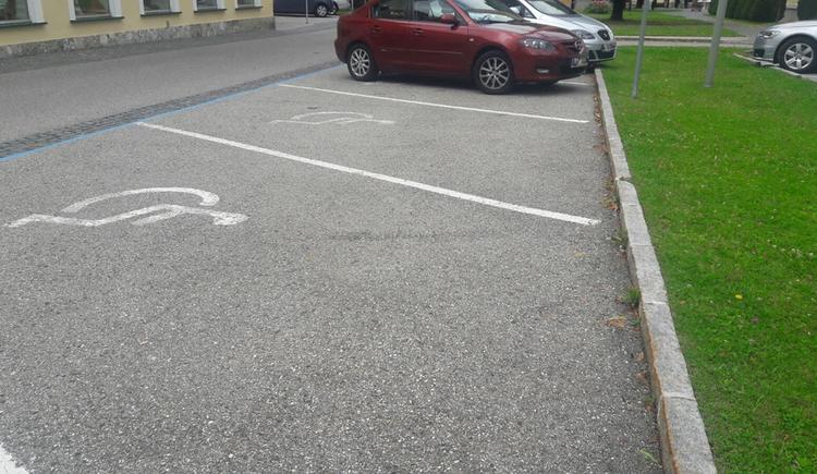 Blick auf die Parkplätze, im Hintergrund parkende Autos, seitlich eine Wiese