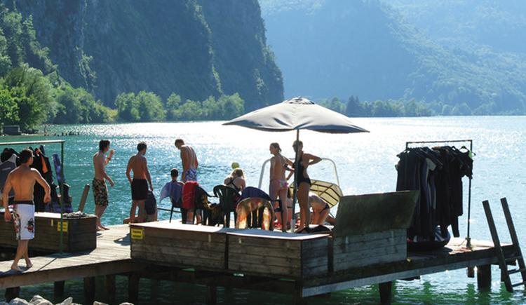 Personen auf dem Steg, im Hintergrund der See und die Berge