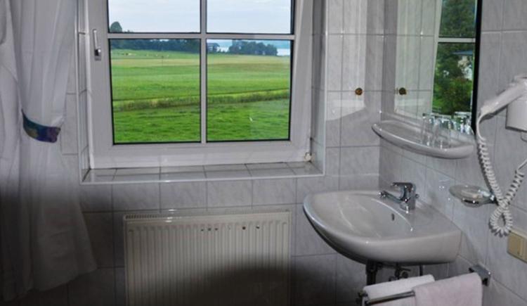 Badezimmer mit Waschbecken, Spiegel, Ablage mit Gläser, Föhn, im Hintergrund ein Fenster mit Blick auf die Landschaft und den See