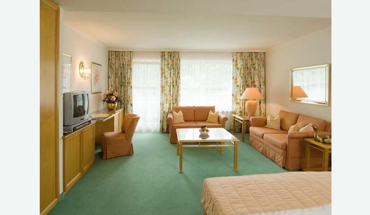 Im Vordergrund ein Teil vom Tett, dahinter Tisch und Sofas, seitlich Fernseher und Stühl, im Hintergrund Fenster und Balkontüre, Teppichboden