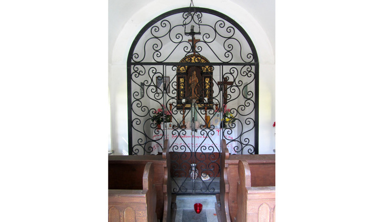 Blick auf den Altar hinter Gitter, Heiligenbilder, Kreuz, seitlich Holzbänke