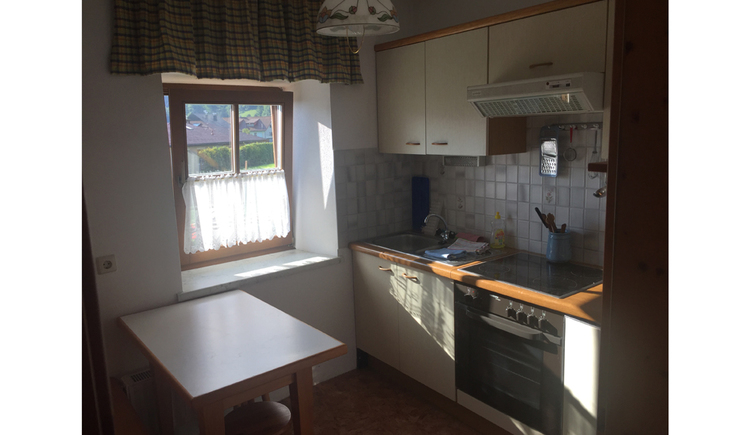 kitchen with a cooker, table, sideward a table and a window