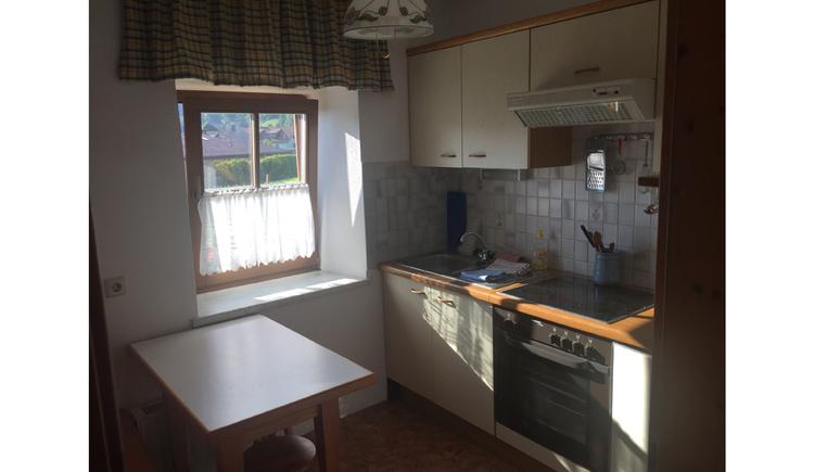 Küche mit Herd, Tisch, seitlich ein Fenster. (© Schachl)