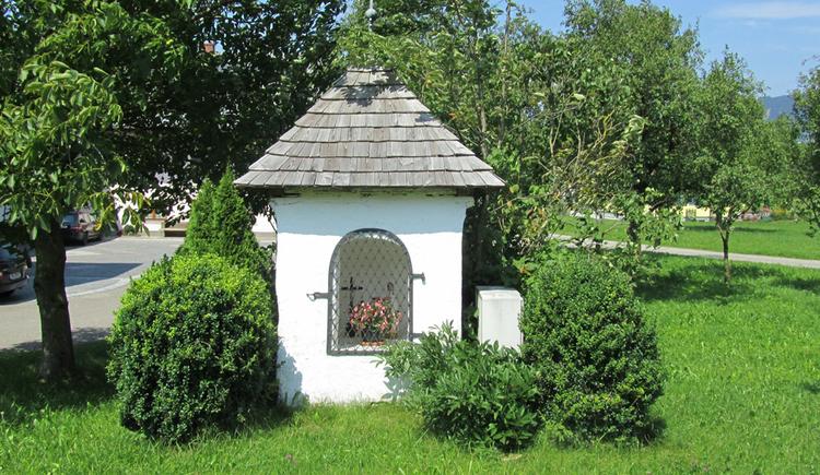 Blick auf eine Kapelle in einer Wiese, dahinter Bäume. (© Annelu Wenter)