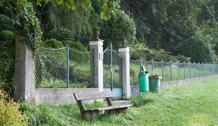 Blick auf eine Zaun, im Vordergrund eine Bank und Wiesen, im Hintergrund die Gräber und Bäume