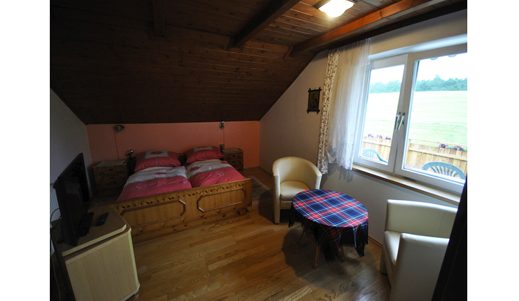 Bedroom with double bed, armchairs and small table, chest of drawers with TV, window