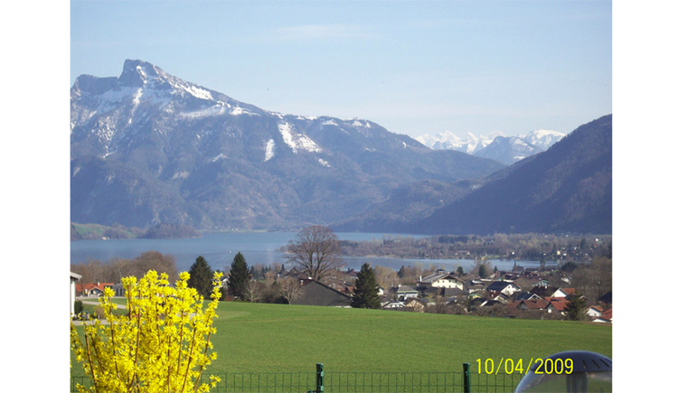 View from the house onto meadows, behind the houses, the lake, snowy mountains in the background