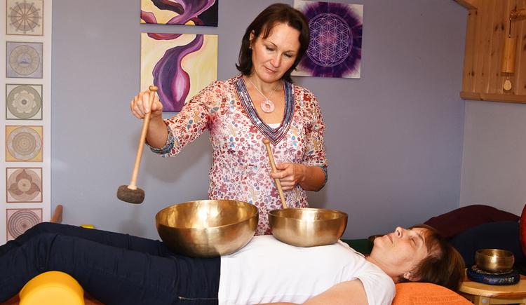 Person liegt mit Klangschalen auf dem Bauch auf einer Liege, Energetikerin im Hintergrund