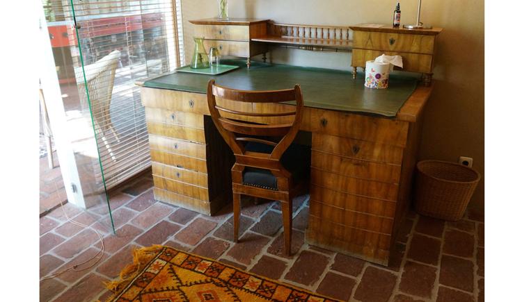 Tisch mit Holzstuhl, Karaffe mit Gläser, seitlich Blick durch die Glastür auf die Terrasse