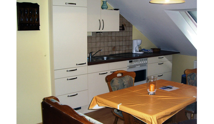 kitchen with sink, cooker and coffee machine, table and chairs in the foreground