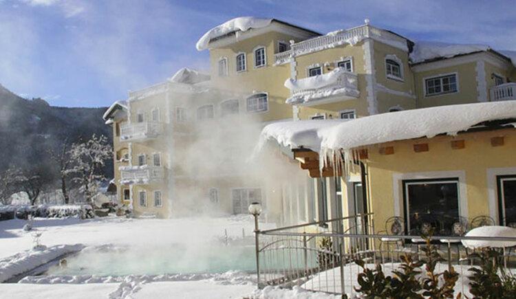 Blick auf das verschneite Hotel mit beheiztem Aussenpool. (© Sperr-Lehrl)