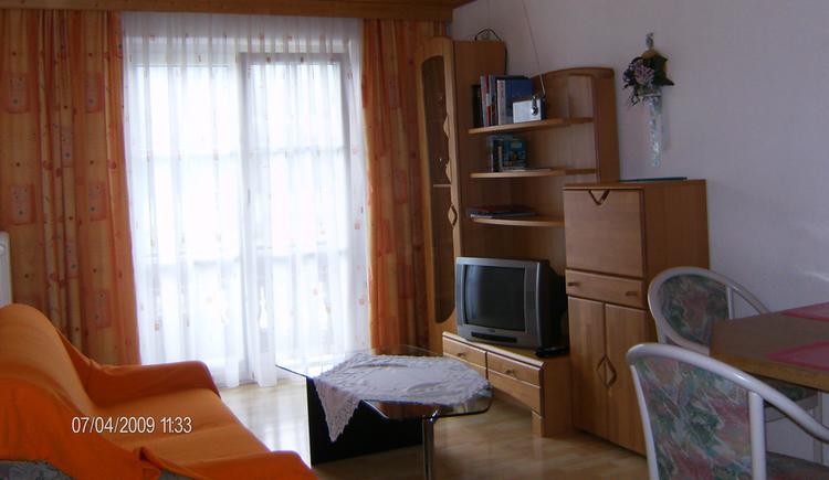 Wohnbereich mit Couch, Tisch, seitlich Stühle und Wohnwand mit Fernseher, Radio, im Hintergrund seitlich Balkontür