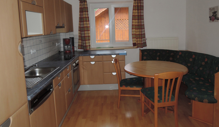 with cooker, sink, coffee maschine, area with bench, table and chairs