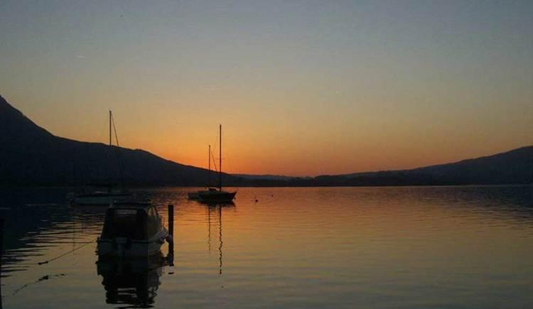 Blick über den Mondsee bei Sonnenuntergang, im Hintergrund die Berge. (© www.mondsee.at)