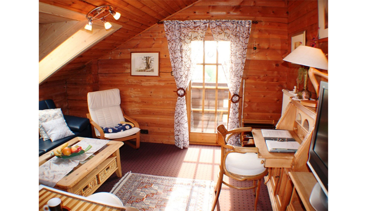 Wohnbereich mit Vollholzmöbel, Couch und Sessel, im Hintergrund eine Balkontür