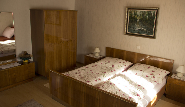 The bedroom is furnished with a double bed, wardrobe and a chest of drawers.