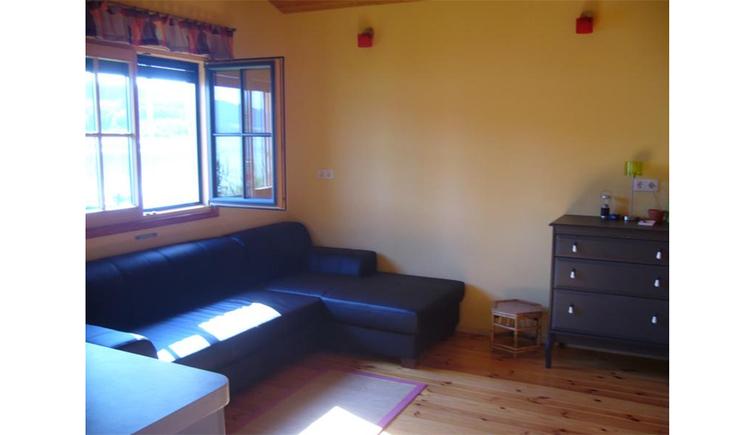Wohnbereich mit Couch, Kommode, seitlich ein offenes Fenster