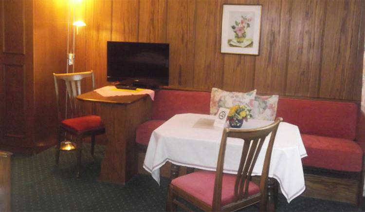 Bank, Tisch und Sesseln, auf einen Tisch steht ein Fernseher, im Hintergrund hängt ein Bild an der Holzwand, seitlich eine eingeschaltete Stehlampe, Teppichboden