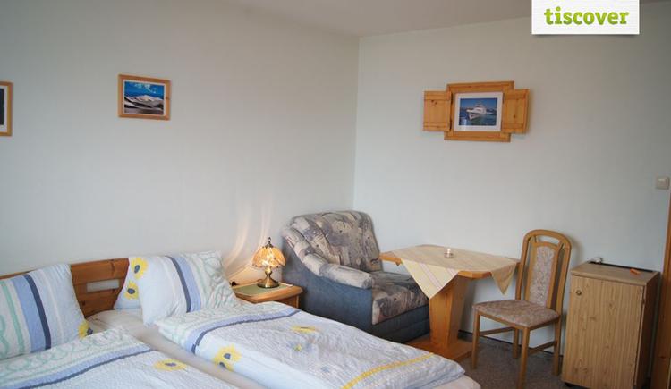 Schlafzimmer mit Doppelbett, Nachtkästchen, Tischlampe, Sessel, Tisch und Stuhl, kleines Kästchen.