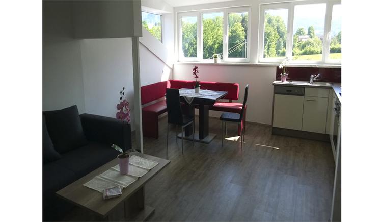 Wohnbereich - seitlich eine Couch mit Tisch, Essplatz mit Eckbank, Stühlen und Tisch, seitlich im Hintergrund die Küche und Fenster