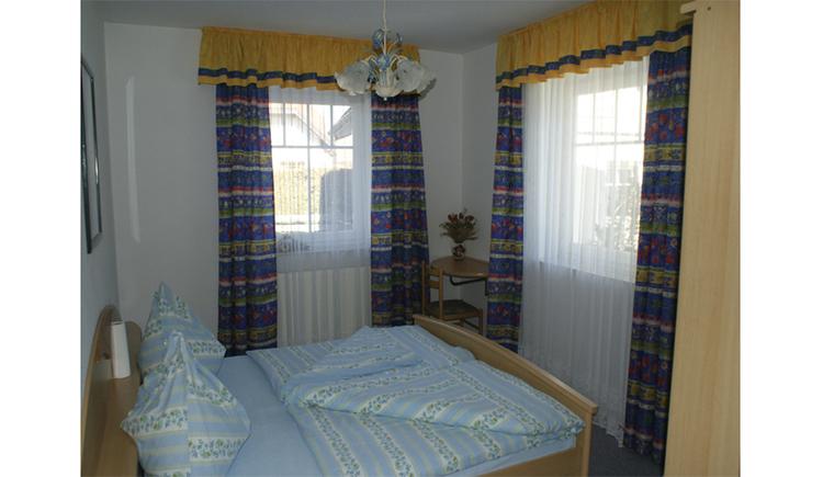 Schlafzimmer mit Doppelbett im Hintergrund Fenster