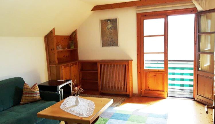 Wohnzimmer mit Couch und offener Balkontüre. (© Familie Schmidleitner)