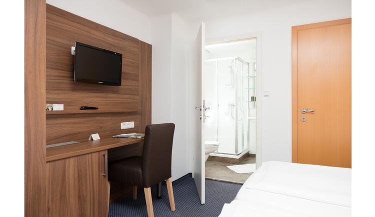 seitlich Sessel, Fernseher an der Wand, im Hintergrund Blick durch die offene Tür ins Badezimmer