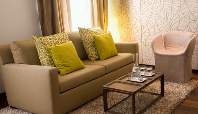 Suite mit Sofa und Polstern, Sessel, Tisch mit Wasserkaraffe und Gläser