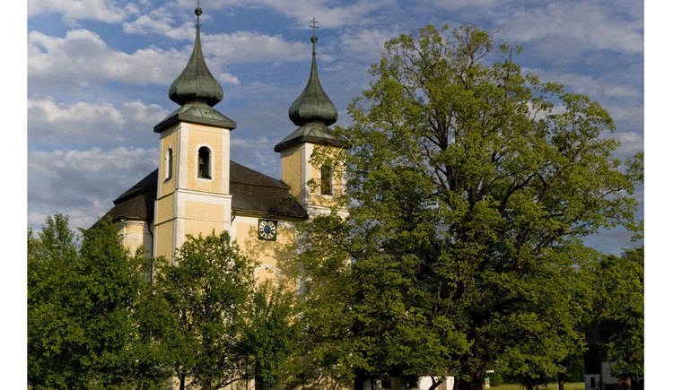 Blick auf die Kirche in St. Lorenz mit ein paar Bäumen im Vordergrund. (© www.mondsee.at)